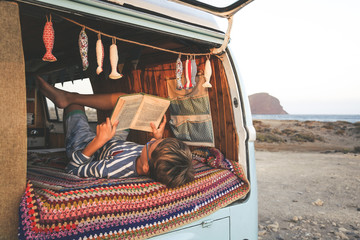 Young boy on retro mini van transport read a book Life inspiration concept with family  minivan adventure trip reading a blast relax moment Student doing homework outdoor camping holiday near the sea