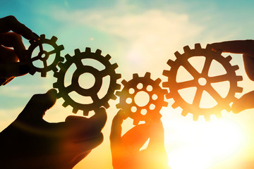 Gears in the hands of people against the sky. teamwork, interaction.