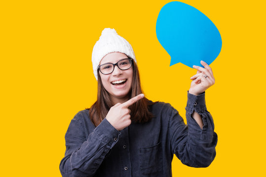 Photo of beautiful young cheerful woman holding speech bubble posing isolated over yellow background wall looking camera pointing
