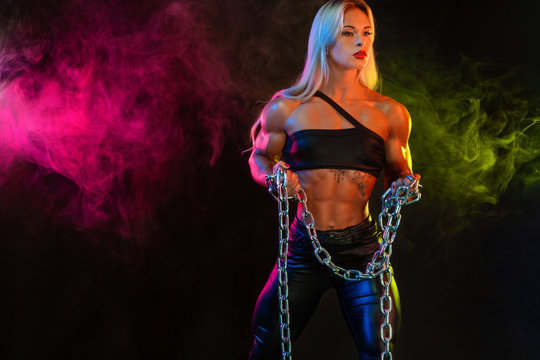 Sporty fit woman bodybuilder, athlete, on background with color smoke holding chains in the hand.