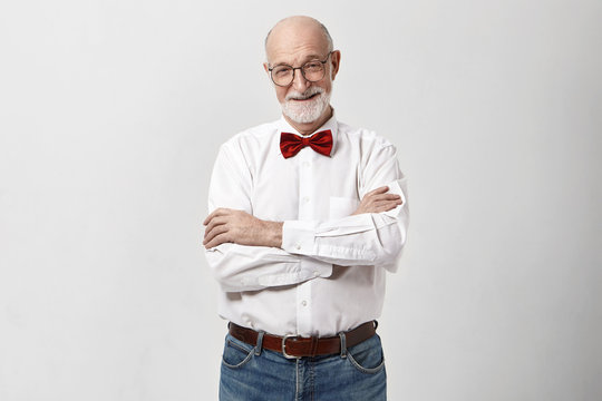Studio shot of cheerful handsome grandfather with beard and bald head smiling, keeping arms crossed on his chest, wearing eyeglasses, jeans, white shirt and bow. Aging, style and elegance concept