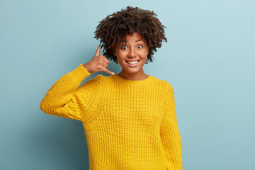 Smiling delighted black woman makes phone gesture, shows call me back sign with hand near ear, pretends talking on mobile phone, dressed in yellow clothes, has glad expression, poses indoor. Wall mural