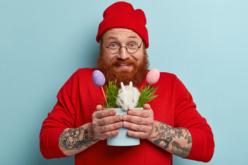 Headshot of ginger positive young man with thick beard holds white fluffy decorative bunny and painted Easter eggs, wears red fashionable clothes, has holiday preparation, giggles happily indoor