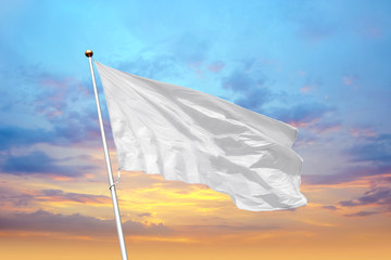 Blank white flag on pole waving in the wind in the background of cloudy sky at sunset. Colorful outdoor picture with empty flag mockup