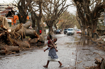 A woman crosses the road with a baby on her back after Cyclone Idai in Beira