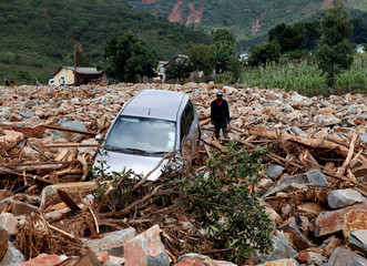 A woman stands besides a car that was swept away with debris by Cyclone Idai in Chimanimani