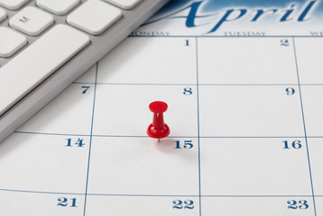 Single red pushpin on April 15 of calendar for tax income due date reminder