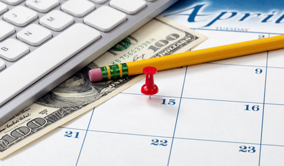 Single red pushpin on April 15 of calendar for tax income due date reminder on desktop