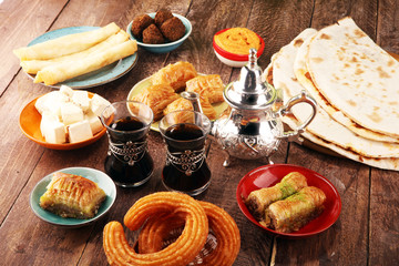 Middle eastern or arabic dishes and assorted meze, concrete rustic background. Turkish Bread or Turkish pizza. Dessert Baklava with pistachio. falafel with hommos.  Halal food. Lebanese cuisine