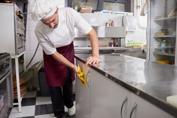 young chef in kitchen wiping cabinets, after closing restaurant.