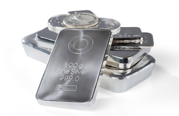 Silver bullion. Cast and minted bars and coins isolated on white background. Selective focus.