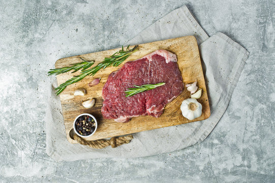 Beef flank steak on a stone Board with rosemary. Gray background, top view, space for text