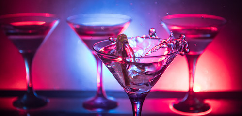 Martini cocktail glass in hand splashing on dark toned smoky background or colorful cocktail in...
