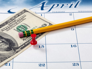 Single red pushpin on April 15 of calendar for tax income due date reminder on desktop with pencil and paper currency