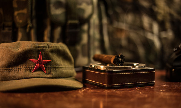 Close up of a Cuban cigar and ashtray on the wooden table. Communist dictator commander table in dark room. Army general`s work table concept.