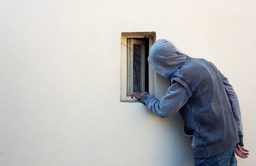 Burglar or thief or robber is looking through the small window and with plan to steal something