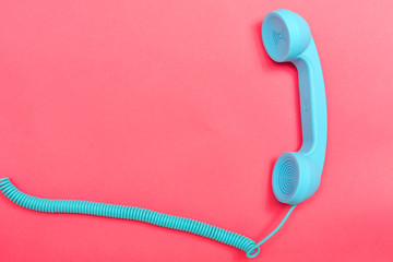 Retro phone on a pink paper background