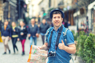 Traveler with trendy look holding map showing thumb up on street full of restaurants and shops of european city – Young man enjoying city vibes taking pictures with photo camera, tourist explore world