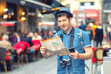 Traveler with trendy look using map on street full of restaurants and shops of european city – Young man tourist sightseeing city taking pictures with photo camera – tourist exploring world