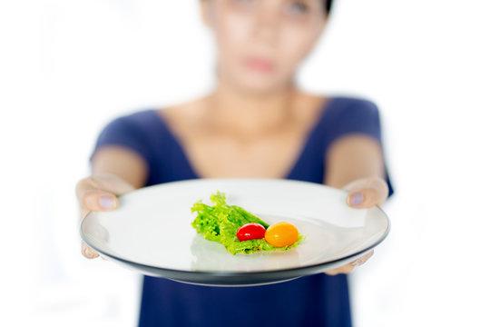 Young woman holds small portion salad on studio
