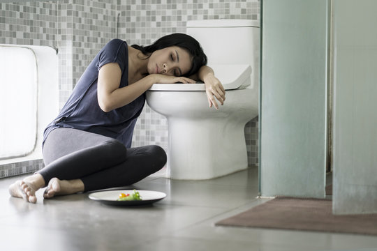 Young woman looks tired after vomiting