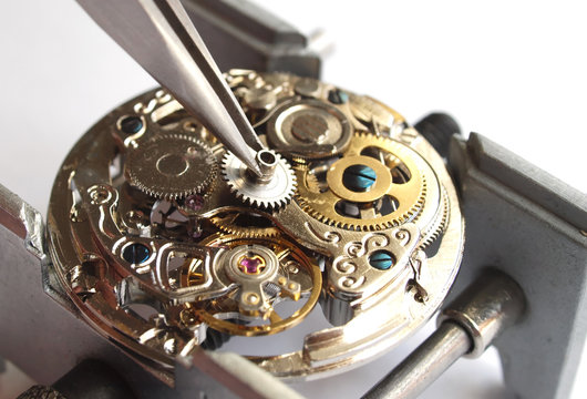 close up of watchmaker repairing old mechanical watch caliber taking small gear with tweezers
