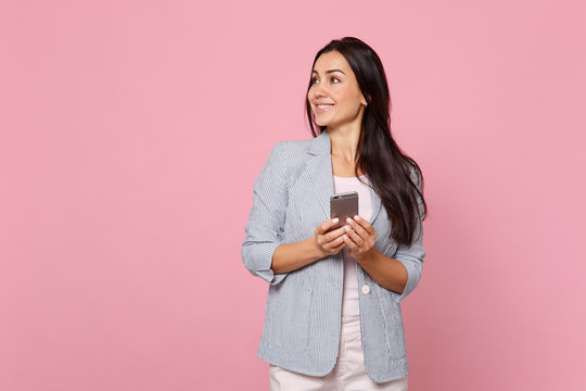 Smiling young woman in striped jacket looking aside using mobile phone, typing sms message isolated on pink pastel background in studio. People sincere emotions, lifestyle concept. Mock up copy space.