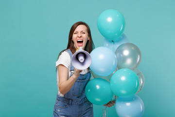 Crazy young woman in denim clothes screaming in megaphone, celebrating and holding colorful air balloons isolated on blue turquoise wall background. Birthday holiday party, people emotions concept.