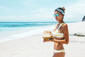 Woman drinking coconut on the tropical beach Wall mural