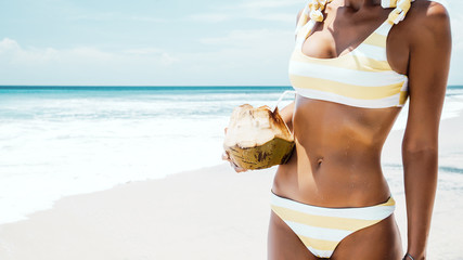 Woman drinking coconut on the tropical beach