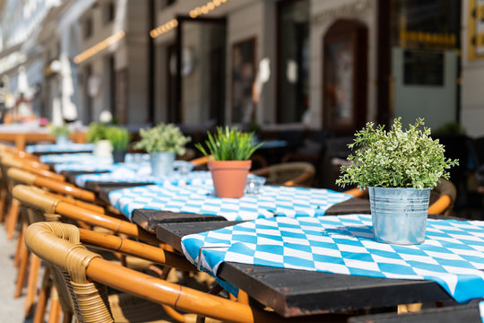 Closeup of empty blue tables outside restaurant cafe chair on sidewalk street green potted flowers plants flowerpot potted setting nobody