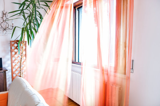 Colorful orange open window curtains blinds in room interior indoors apartment flowing in wind in Italy