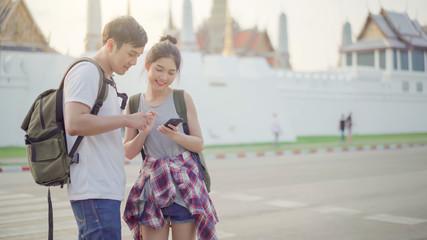 Asian Thai pretty couple using smartphone while travel in Bangkok Thailand