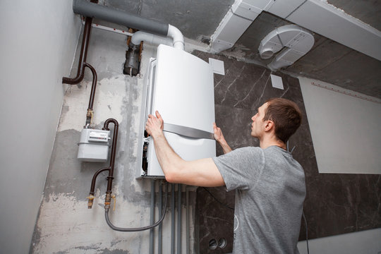 Installation and setting the new gas boiler for hot water and heating. Technician servicing the house heating system.
