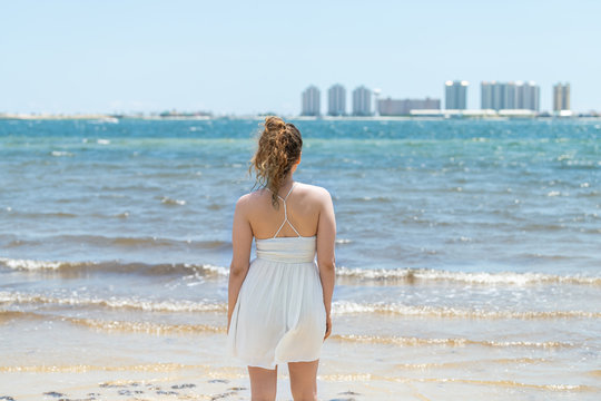 Young woman back standing in white dress on beach bay shore in Florida with cityscape skyline during day of Pensacola