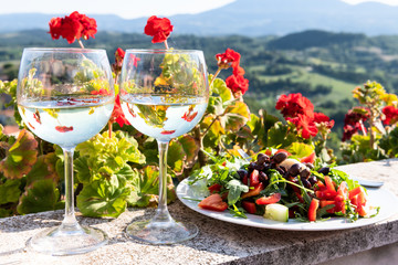 Closeup of arugula salad with olives and white wine two glassses plate on balcony terrace by red geranium flowers in garden outside in Italy in Tuscany Fototapete