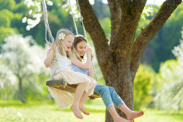 Two cute sisters having fun on a swing in blossoming old apple tree garden outdoors on sunny spring day.