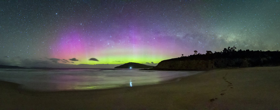 Aurora Australis or Southern Lights and the setting Milky Way over a beach in Tasmania.