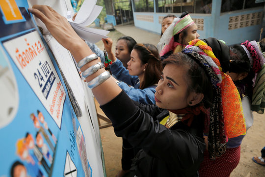 An ethnic Kayan woman, also known as a long neck villager, checks her name at the polling station in Ban Huadua school to cast her vote for the general election in Mae Hong Son