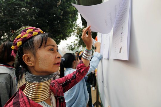 An ethnic Kayan woman also known as a long neck villager checks her name at the polling station in Ban Huadua school to cast her vote for the general election in Mae Hong Son