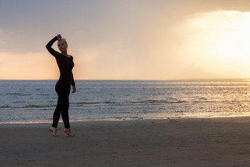 girl at sunset on the beach, lady in black clothes, barefoot woman