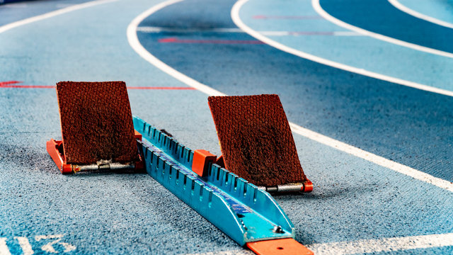 Athletics starting blocks on race blue track