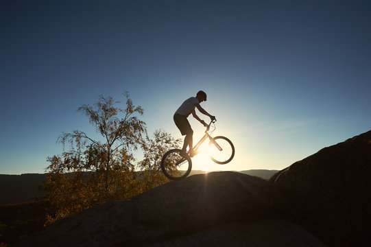 Young cyclist riding on back wheel on trial bike. Sportsman rider making acrobatic stunt on the edge of big boulder on the top of mountain at sunset. Concept of extreme sport active lifestyle