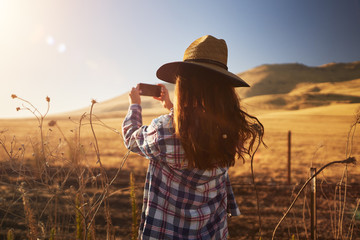skinny girl wearing hat taking photo of rural california landscape