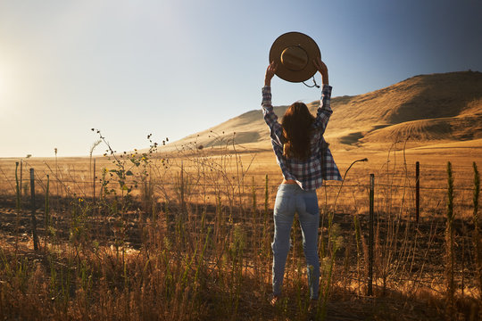 woman wearing jeans and flannel from behind looking at view of rural california landscape holding up hat in air