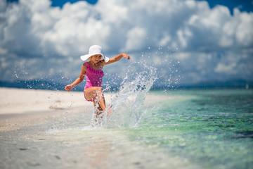 Happy girl playing splashing in exotic ocean island
