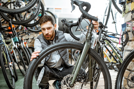 Man choosing new bicycle to buy standing in the shop with lots of bicycles and sports equipment indoors