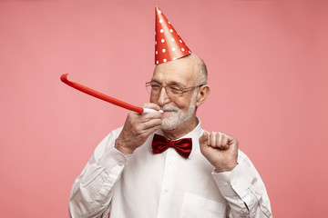 Fototapeta Portrait of cheerful good-looking elderly retired man with thick gray beard standing at pink studio wall, wearing nice elegant clothes and holiday hat, blowing whistle, celebrating his birthday obraz