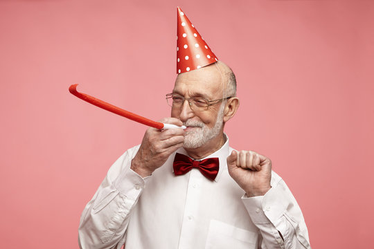 Portrait of cheerful good-looking elderly retired man with thick gray beard standing at pink studio wall, wearing nice elegant clothes and holiday hat, blowing whistle, celebrating his birthday