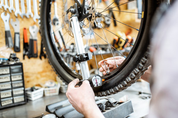 Man aligning bicycle wheel tensing spokes with a special key at the working place of the workshop, close-up view